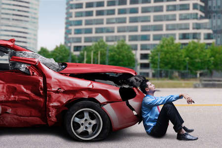 damaged car: Young man sitting in front of a damaged car while waiting help after collision on the road