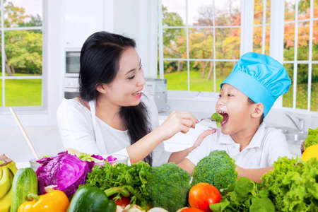 mom son: Image of a young mother feeding her son with fresh vegetables in the kitchen at home Stock Photo