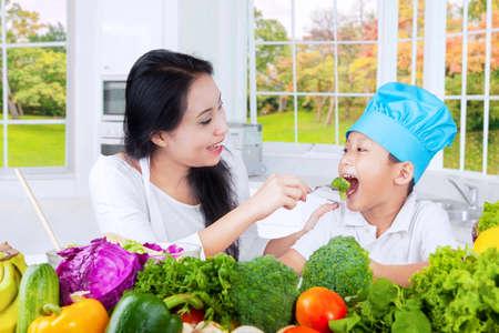 mama e hijo: Imagen de una joven madre de alimentar a su hijo con las verduras frescas en la cocina en el hogar
