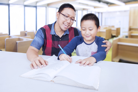 Male elementary school student studying in the classroom and write on the book with male tutor Banco de Imagens