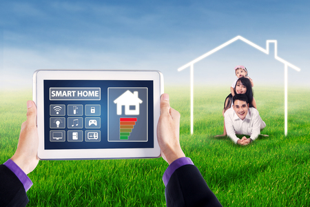 temperature controller: Image of smart home system applications on the digital tablet with happy Asian family lying at field under a house symbol