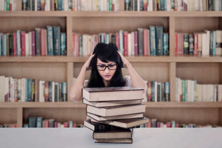 stressing: Beautiful female student stressing out at library Stock Photo