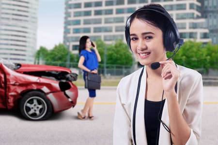 telephone call: Friendly female operator smiling at the camera while wearing headset to talk with her customer after collision on the road Stock Photo