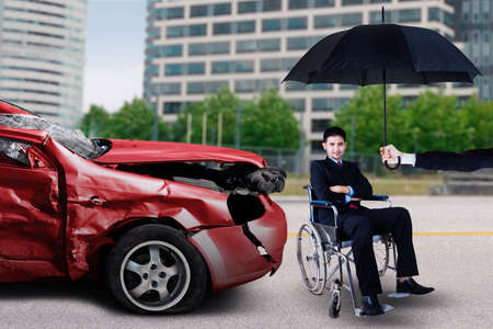 recovery: Disabled businessman sitting on wheelchair under umbrella in front of a damaged car