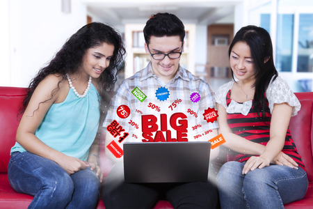 advertisement: Three multi ethnic people sitting on the sofa while using laptop with online discount icon