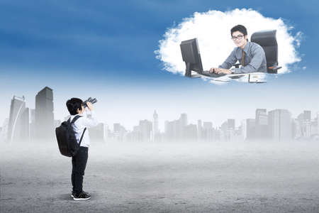 asian children: Male student using binoculars to see a male entrepreneur working with computer on the cloud at sky Stock Photo