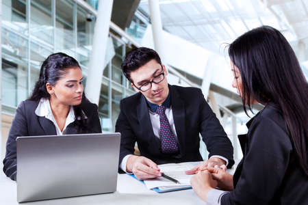 new employee: Portrait of two business people showing an employment contract on a new employee in the office Stock Photo