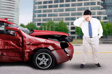 asian guy: Portrait of overweight person standing in front of a damaged car and looks confused, shot on the road
