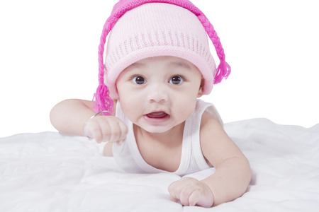 Image of a funny baby boy lying down on the bed while wearing hat and  looking 1633de5e6ef1
