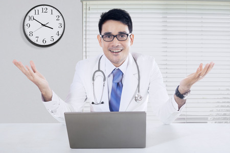 welcome desk: Friendly doctor with welcome gesture sitting in the office with laptop on desk and a clock on the wall