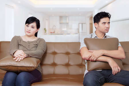 family fight: Portrait of two young couple having problems in marriage and sitting on the sofa at home Stock Photo