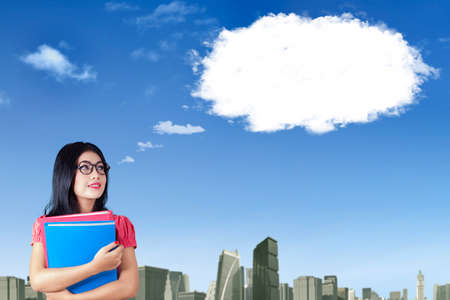 soñando: Imagen de feliz de la hembra en posesión de documentos y con gafas, mirando a la nube