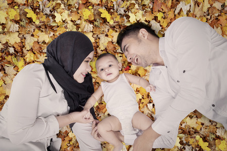 lying on leaves: Close up of happy muslim family and their baby lying down on the autumn leaves at the park