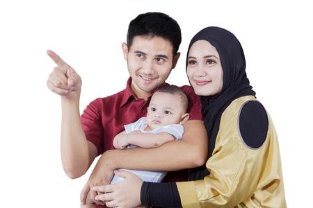 Portrait de parents arabes et leur fils en regardant quelque chose dans le studio, isolé sur fond blanc Banque d'images - 62606121