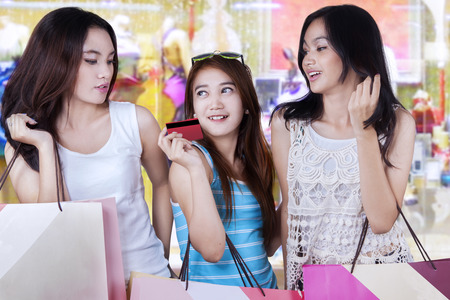 buyer: Portrait of three young girls holding a credit card while carrying shopping bags in the shopping center