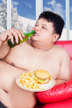 hombre tomando cerveza: Retrato de hombre gordo sentado en el sofá mientras disfruta de la cerveza fresca y comida chatarra en temporada de invierno