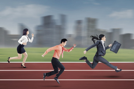Three young businesspeople running on the track to compete together, shot outdoors
