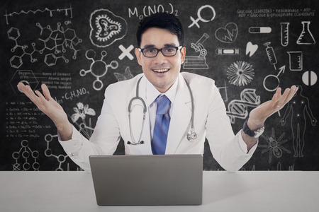 welcome desk: Friendly physician smiling at the camera with welcome gesture and laptop on desk, shot in the lab