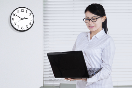 working on laptop: Pretty young woman standing in the office while working with laptop and a clock on the wall Stock Photo