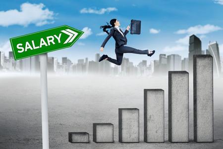 persona saltando: El concepto de crecimiento salarial. Trabajador de sexo femenino que salta por encima de un gráfico de crecimiento salarial con una palabra salario en el poste indicador