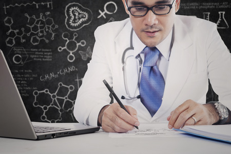 Close up of a male specialist doctor writing a medicine recipe with laptop and doodles background