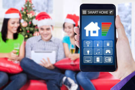 mobile app: Hand holding a mobile phone with smart home system applications, shot with three young people wearing santa hat and using digital tablet in christmas day