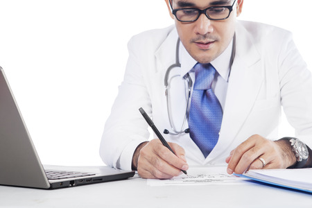 physician: Close up of a male medical doctor writes a prescription on the paper with laptop on the table