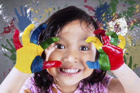 fingerpaint: Beautiful little girl smiling at the camera while showing her hands painted in colorful