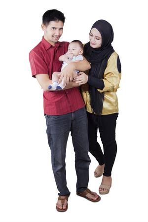 Full length of two muslim parents and their baby standing in the studio, isolated on white background