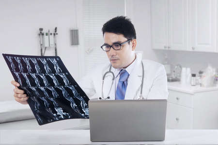 roentgen: Young physician looking at x-ray or roentgen image with laptop on desk, shot in the clinic room