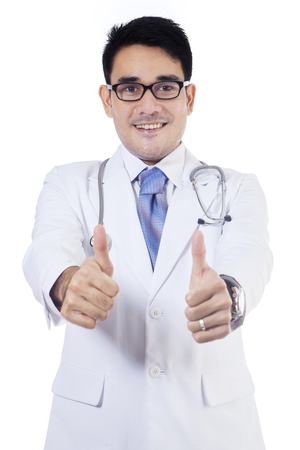 man doctor: Portrait of a young male doctor giving two thumbs up while wearing glasses in the studio, isolated on white background Stock Photo