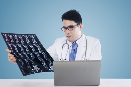 roentgen: Asian doctor looking at a roentgen image with laptop computer on the table