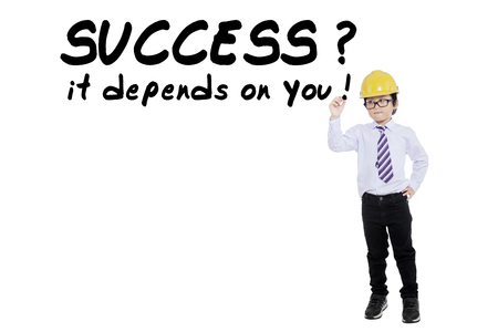 depends: Image of a little boy wearing hardhat and writing text of success it depends on you, isolated on white background Stock Photo