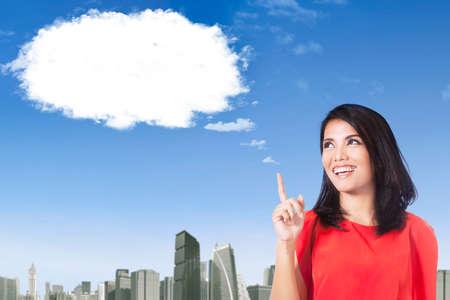 soñando: Mujer joven alegre idea de pensamiento mientras apunta a la nube y sonriente