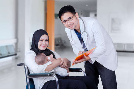 asian medical: Portrait of male doctor talking with young mother sitting on the wheelchair, shot in the hospital Stock Photo
