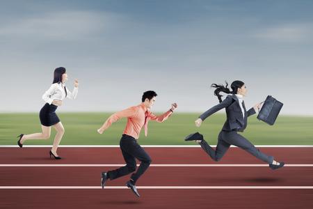 jovenes emprendedores: Imagen de tres jóvenes empresarios que se ejecuta en la pista para competir juntos Foto de archivo
