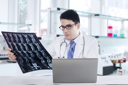 roentgen: Picture of a male physician looking at x-ray or roentgen image with laptop on the table, shot in the laboratory