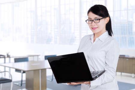 obrero trabajando: Trabajador de sexo femenino hermosa que se coloca en el sitio de la oficina mientras se trabaja con el ordenador portátil