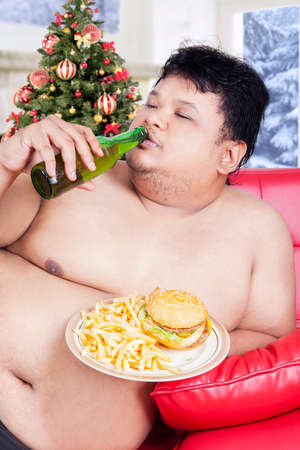potbelly: Portrait of lazy overweight man sitting on the sofa while enjoying fresh beer and fast food at christmas day