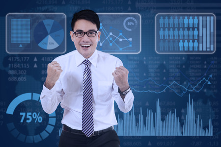 profit celebration: Portrait of a cheerful young businessman celebrating his winning with financial graph background Stock Photo