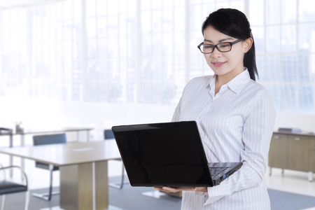 working on laptop: Young businesswoman standing in the office room while using laptop computer and wearing glasses