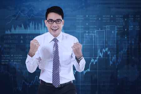 arms up: Image of successful businessman celebrating his success with financial statistics and arms up