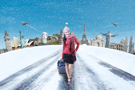 winter holiday: Beautiful woman travelling to the worldwide monument while carrying suitcase in winter holiday