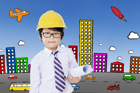 Little boy wearing glasses and holding a blueprint with a city background Stock Photo