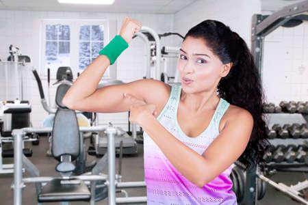 strength training: Indian young woman pointing at her bicep in the fitness center while wearing sportswear