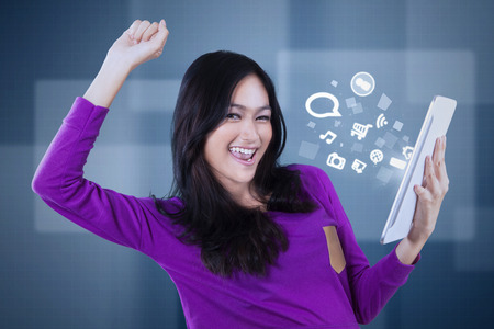 media gadget: Image of a joyful teenage girl holding a digital tablet with social network icon Stock Photo