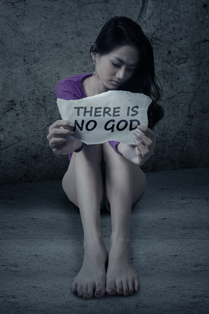 atheist: Image of atheist teenage girl sitting on the floor while holding a paper with text THERE IS NO GOD