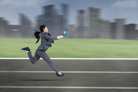 Young businesswoman running on track while wearing formal suit and holding laptop computer Stok Fotoğraf