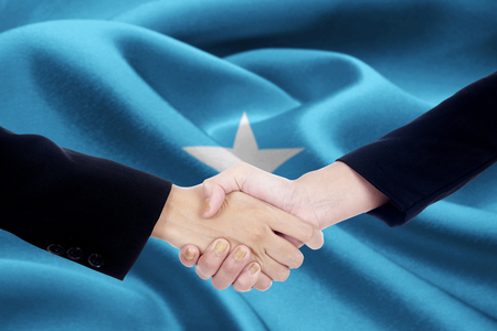 Picture of a collaboration handshake with two people hands closing a meeting by shaking hands with flag of Somalia