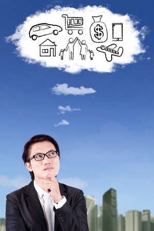 imagines: Portrait of Asian businessman wearing glasses and imagines his wish while looking at the cloud